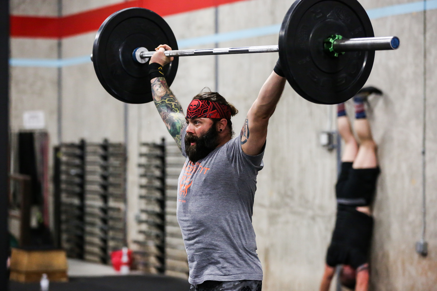 A man performing an olympic weightlifting movement.