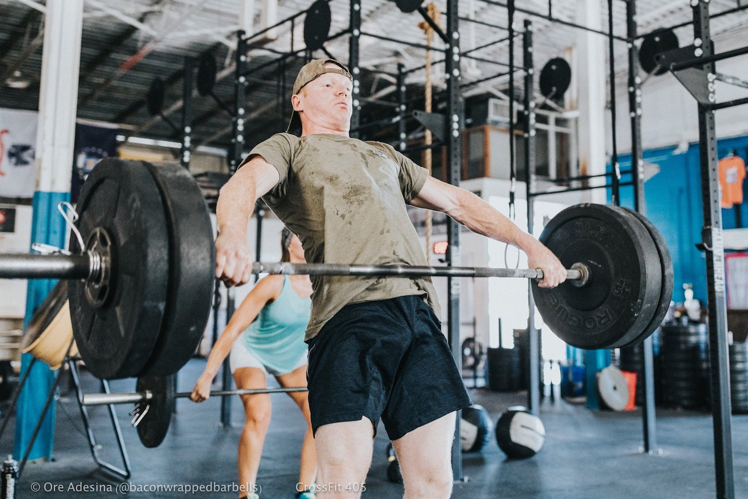 A young man performing an olympic weightlifting movement.
