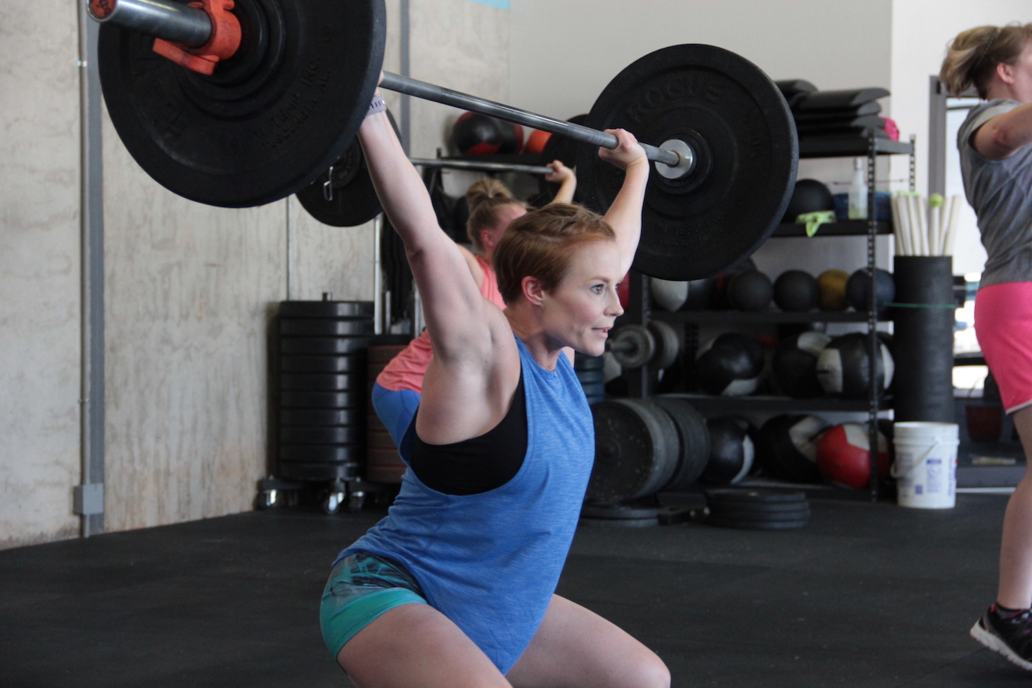 A woman performing an olympic weightlifting movement.