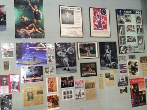 photos of lifters and martial artists who worked with Miller, news articles on a wall